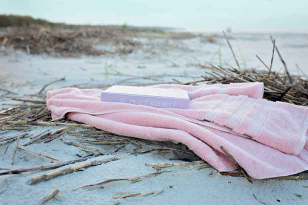 book on pink textile on sand during day