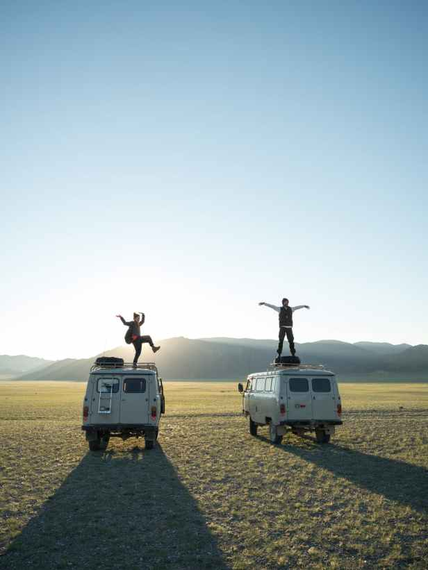 travelers standing on vans in remote valley