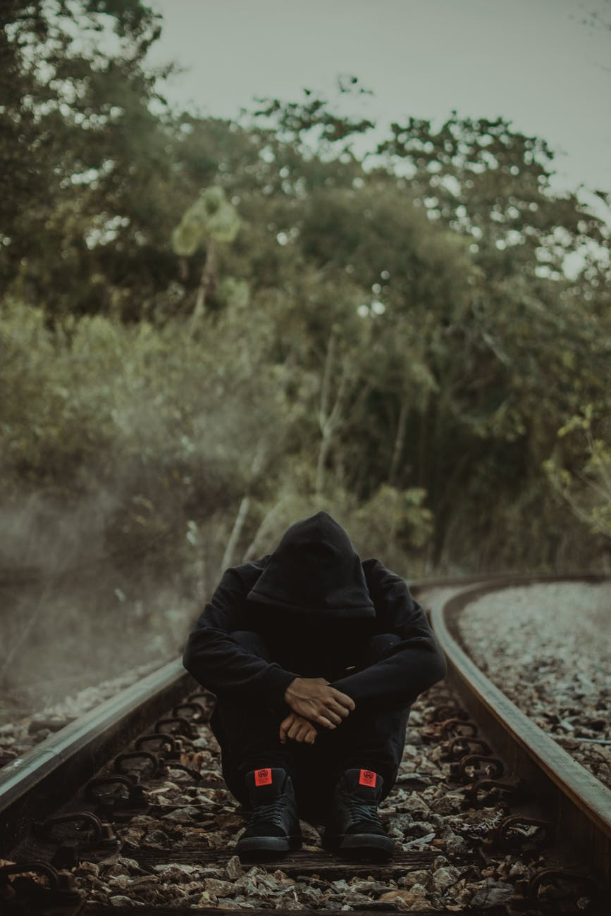 photo of man sitting alone in the middle of a train track